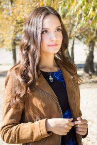 Portrait of young beautiful brunette woman in park on a sunny autumn day